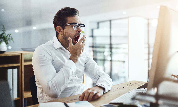 A man yawning at his desk