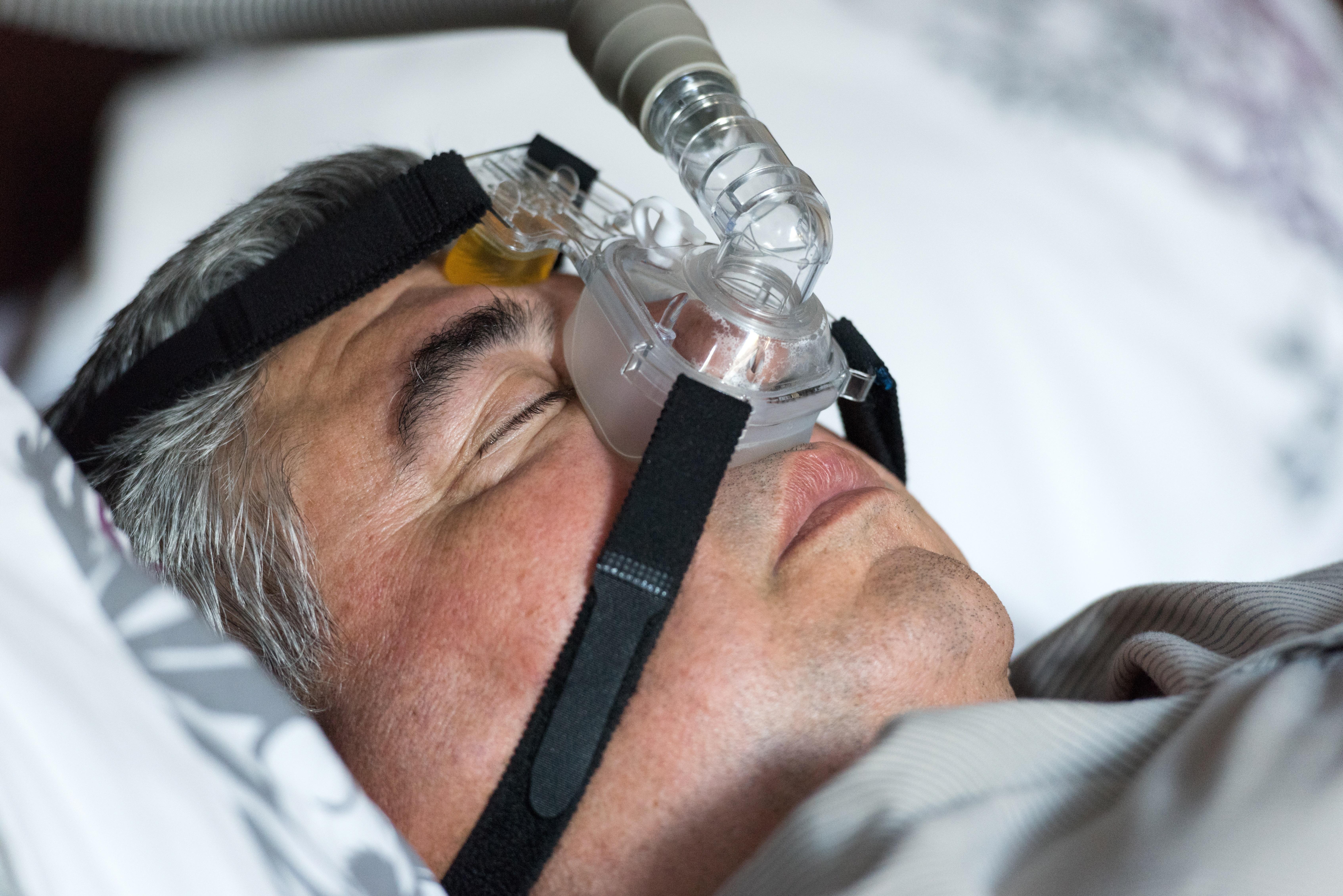 A man using a CPAP machine to sleep