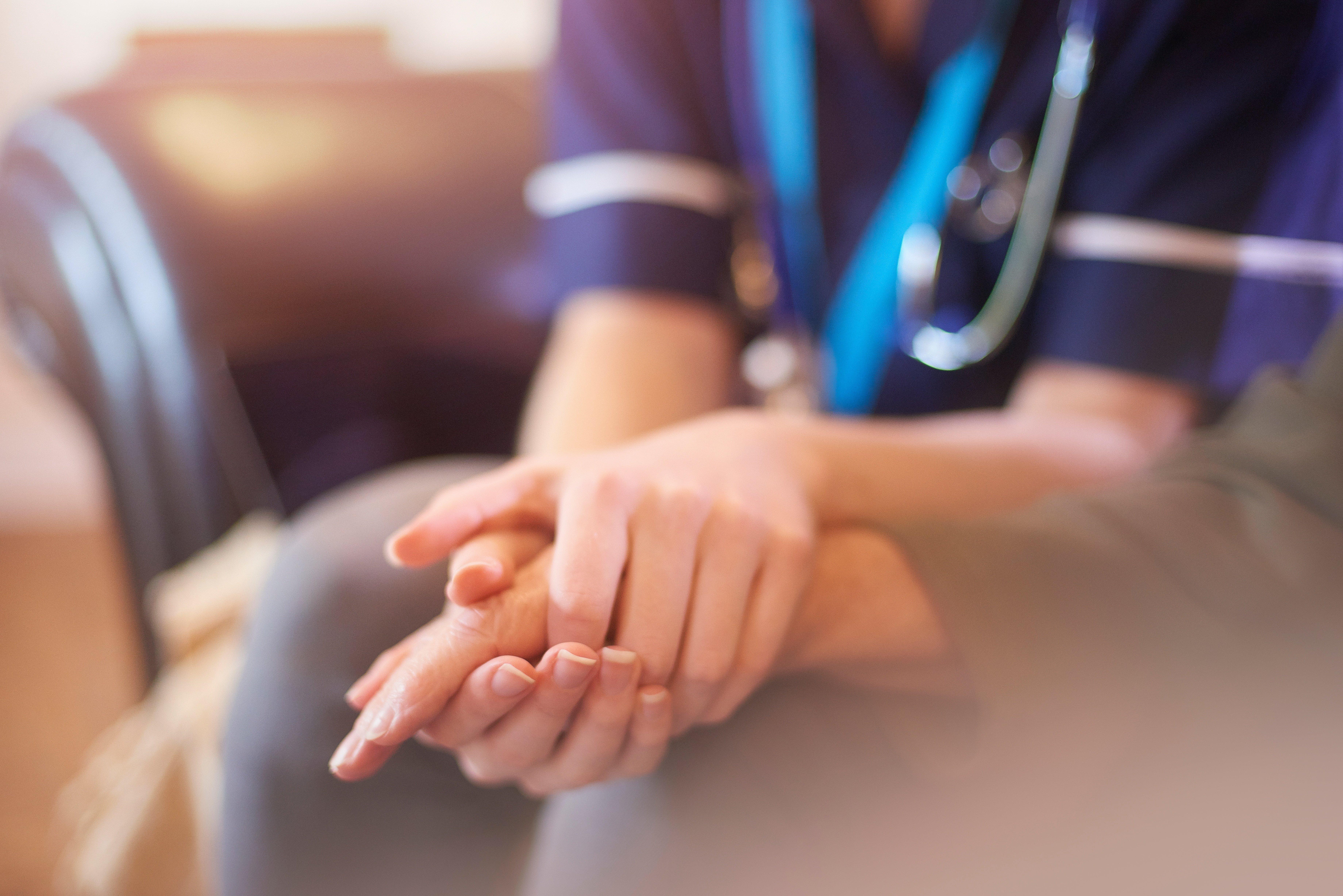 A nurse holding a palliative care patients hand