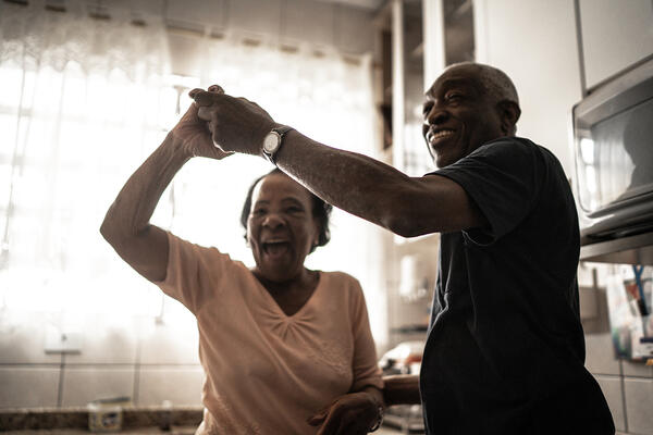 a senior couple dancing in their kitchen