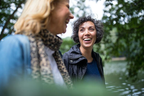 Happy mature woman looking at a friend in forest