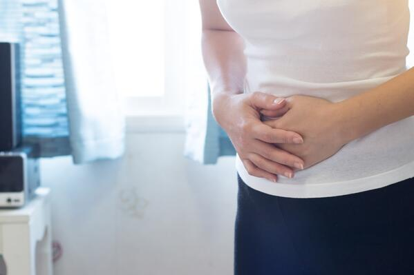 A woman holding her stomach in her bathroom